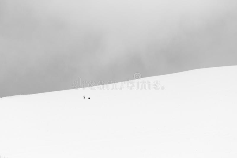 Een zeer minimalistic mening van twee verre die mensen over een berg door sneeuw, dichtbij een omheining wordt behandeld, die pre stock afbeelding