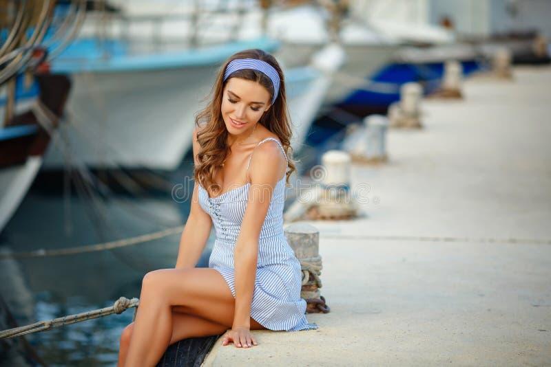 Een zeer mooi sensueel en sexy meisje in een blauwe gestreepte kleding i stock foto