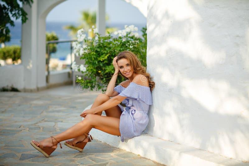 Een zeer mooi sensueel en sexy meisje in een blauwe kleding is sittin royalty-vrije stock foto's