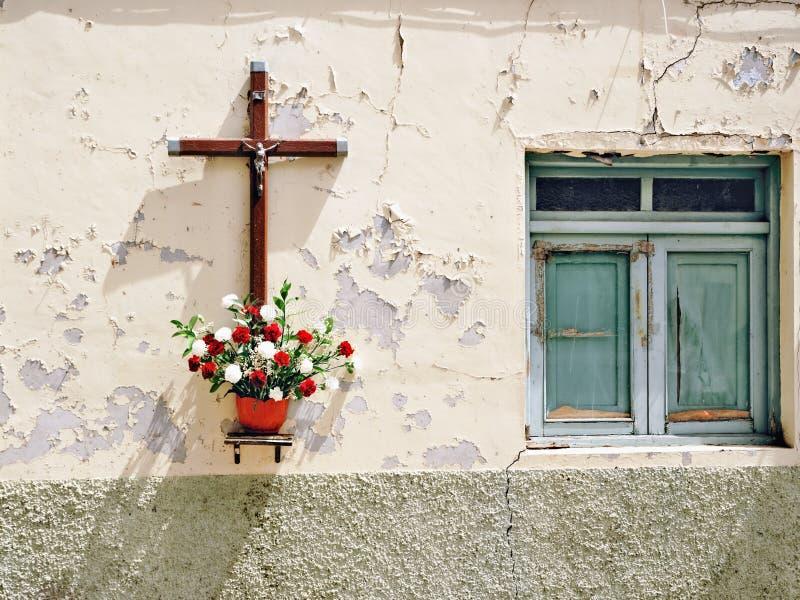Een zeer oude dilapidated huismuur met afgebladderd room-gekleurd pleister, een Kruis met Jesus Cristus en Bloemen stock afbeeldingen