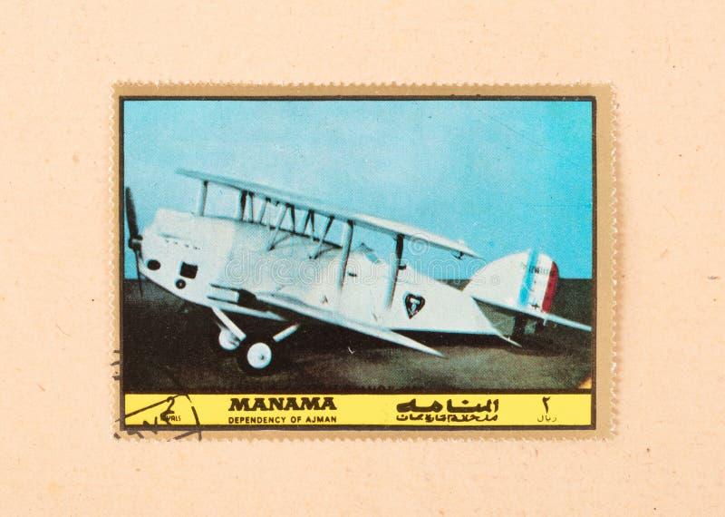 Een zegel in de V.A.E wordt gedrukt toont een oud vliegtuig, circa 1980 die stock foto's