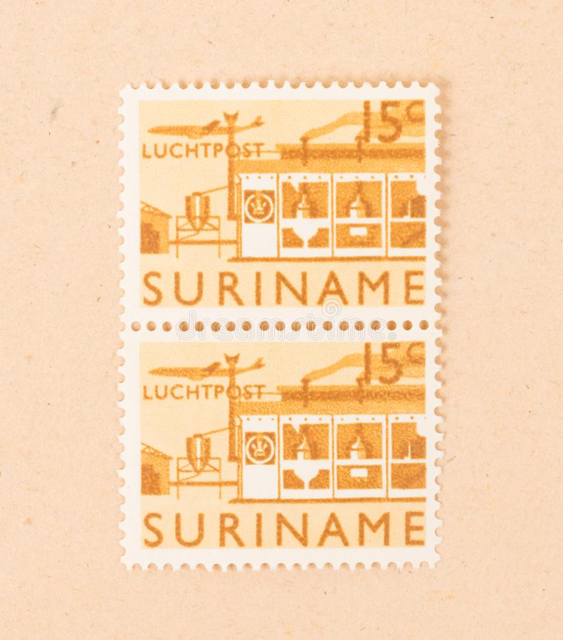 Een zegel die in Suriname wordt gedrukt toont een fabriek, circa 1970 royalty-vrije stock fotografie