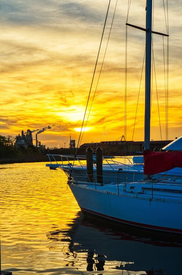 Een zeilboot met een mooie zonsondergang achter het stock foto