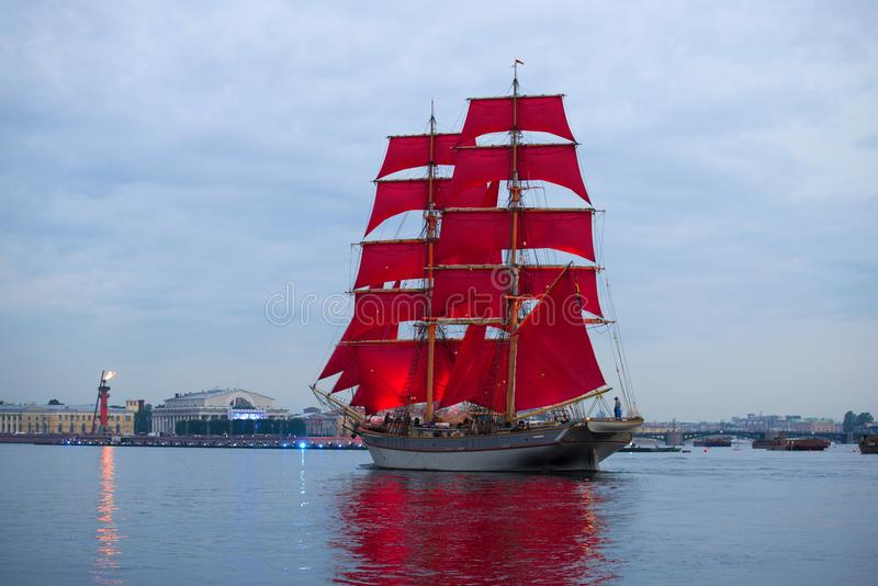 Een zeilboot met scharlaken zeilen tegen de achtergrond van de pijl van Vasilyevsky Island ` Scharlaken zeilen ` royalty-vrije stock afbeeldingen