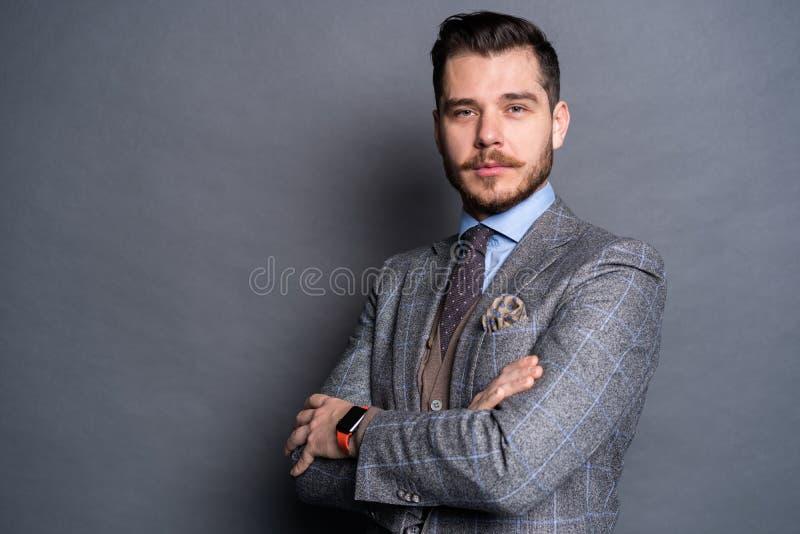 Een zekere elegante knappe jonge mens die zich voor een grijze achtergrond in een studio bevinden die een aardig kostuum dragen stock foto's