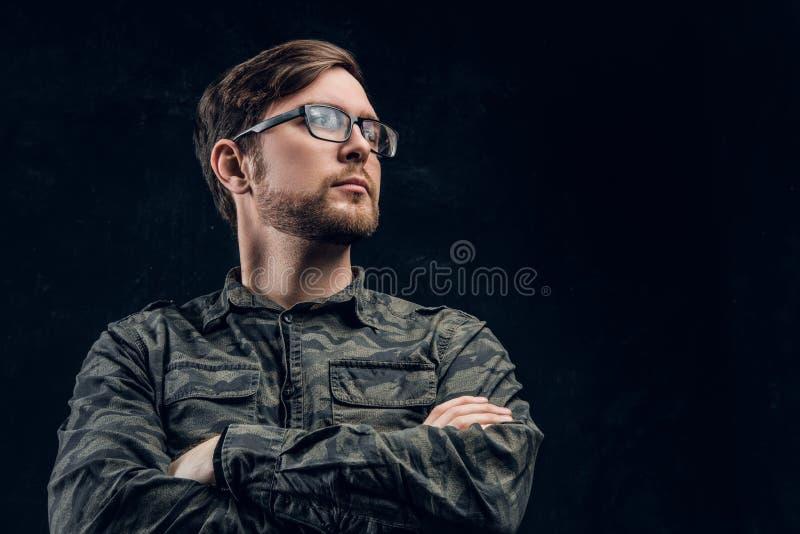 Een zekere hakker in het modieuze militaire overhemd stellen met gekruiste handen en zijdelings het kijken royalty-vrije stock fotografie