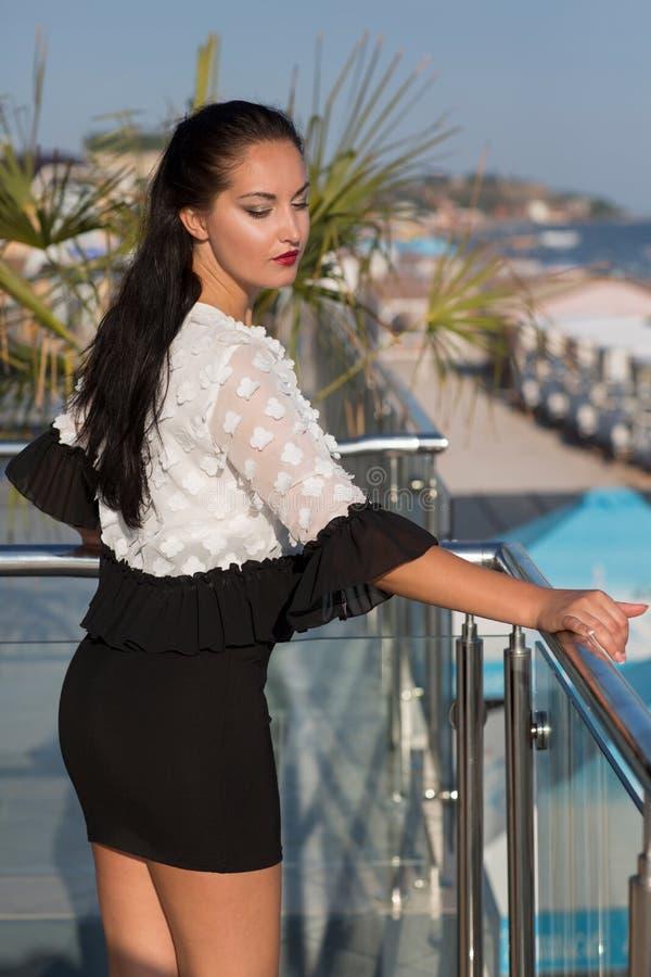 Een zekere vrouw op een zonnige strandachtergrond Een schitterend wijfje in een zwart-witte kleding op een glasterras Manierleven stock fotografie