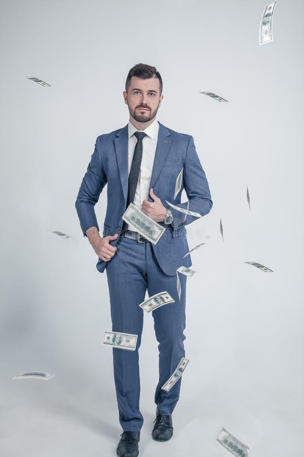 Een zekere zakenman loopt ernstig op de achtergrond van geld gekleed in een kostuum die zich op een witte achtergrond bevinden royalty-vrije stock afbeelding