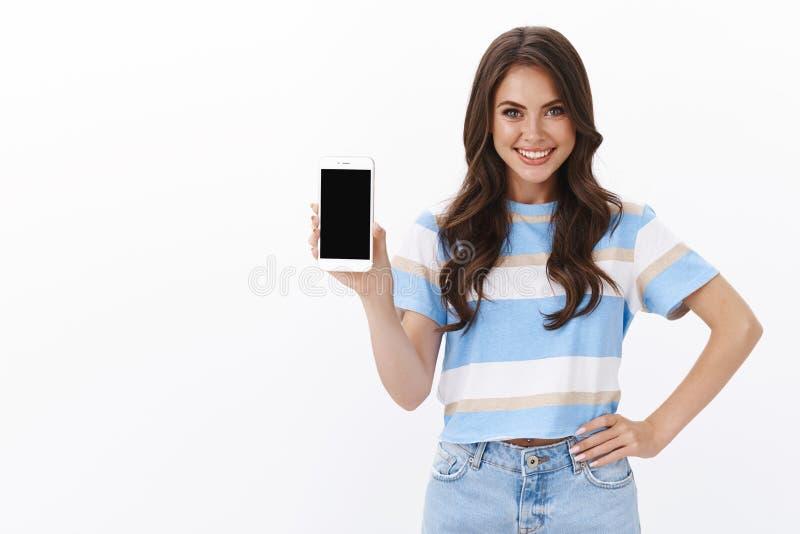 Een zelfverzekerd, goed uitziend brunet met krullend haarkapje laat het smartphone-scherm zien, introduceer nieuwe, coole, modern royalty-vrije stock fotografie