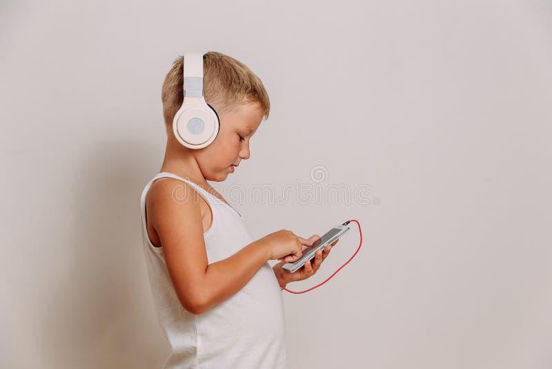 Een zeven-jaar-oud kind luistert aan muziek door grote ware groottehoofdtelefoons op een witte achtergrond Het kind gebruikt een  royalty-vrije stock afbeeldingen