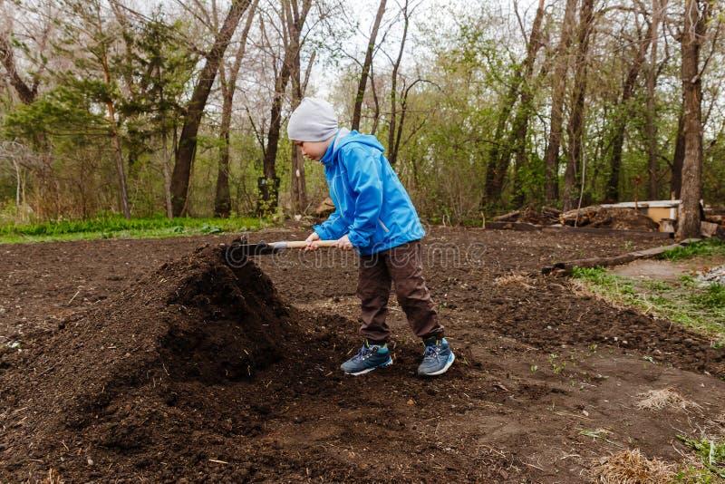 Een zeven-jaar-oude jongen in een blauwe windjekker en een hoed graaft de grond met een sapper schop in de tuin stock foto's