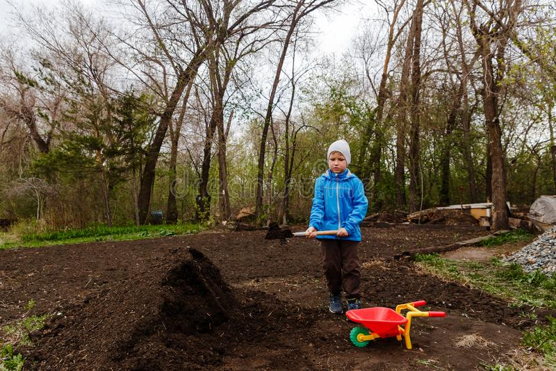 Een zeven-jaar-oude jongen in een blauwe windjekker en een hoed werpt aarde met een sapper schop in een kar in de tuin royalty-vrije stock afbeeldingen