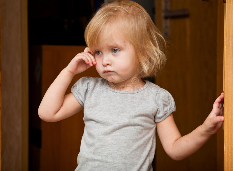 Een ziek meisje is dichtbij de deur stock afbeelding