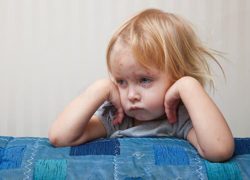 Een ziek meisje zit dichtbij het bed royalty-vrije stock foto