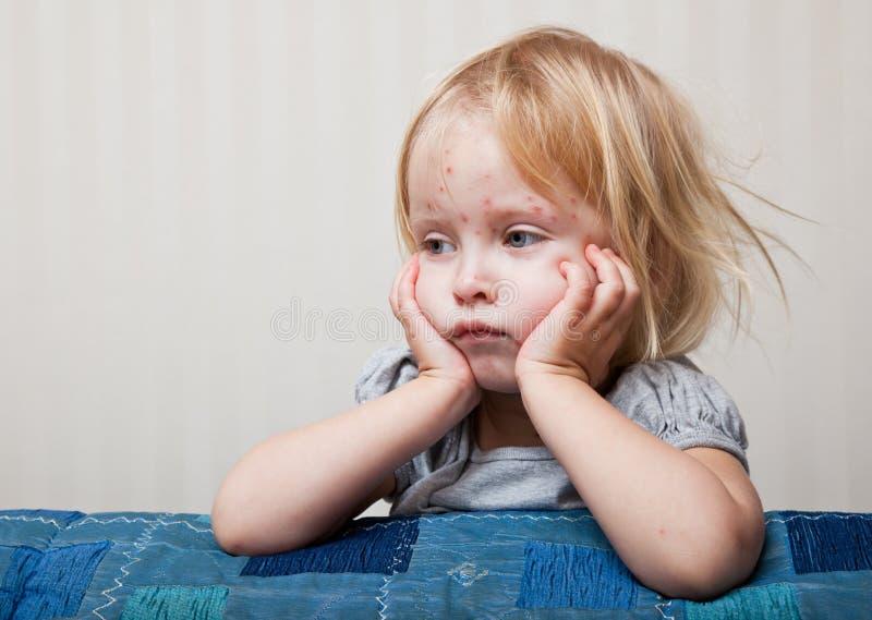 Een ziek meisje zit dichtbij het bed royalty-vrije stock afbeeldingen