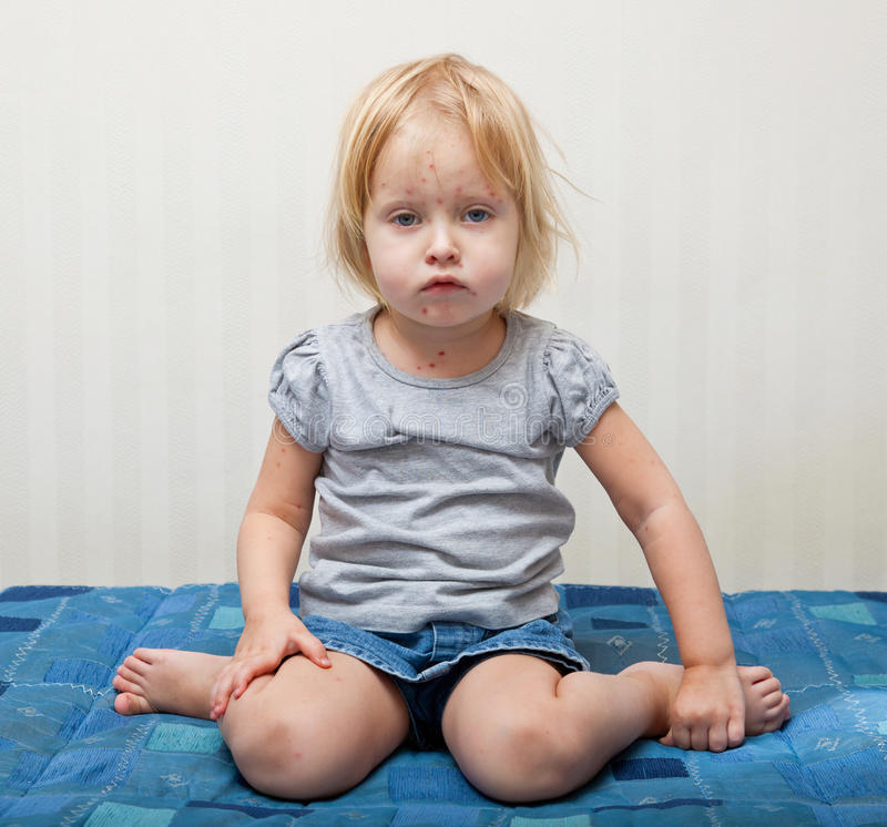 Een ziek meisje zit dichtbij het bed stock foto
