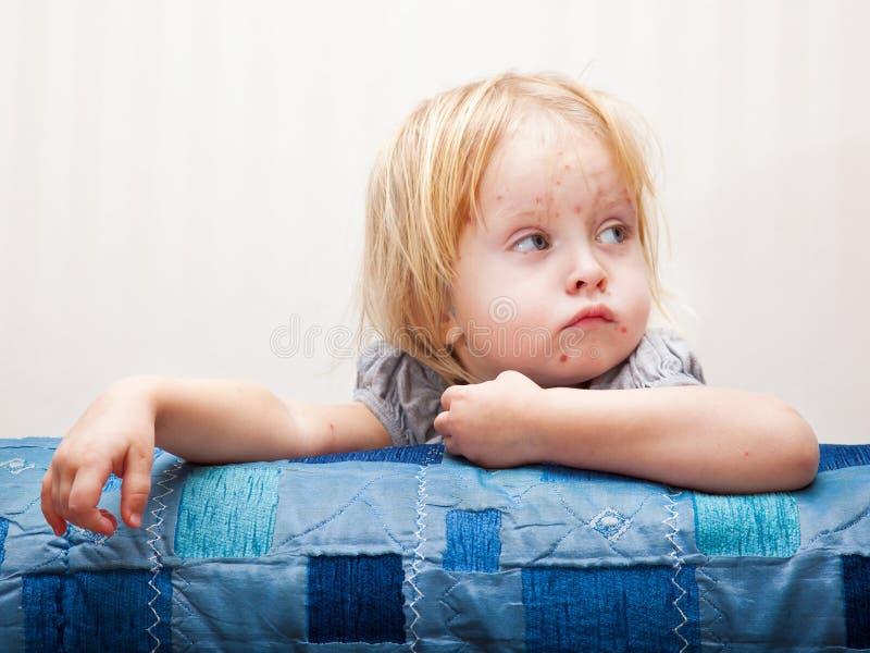 Een ziek meisje zit dichtbij het bed stock foto's