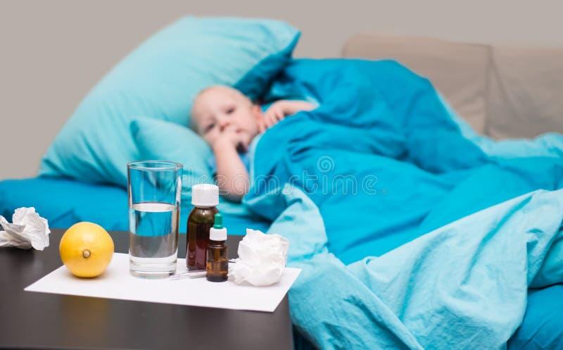 Een zieke baby die in bed liggen en thermometer bekijken stock foto