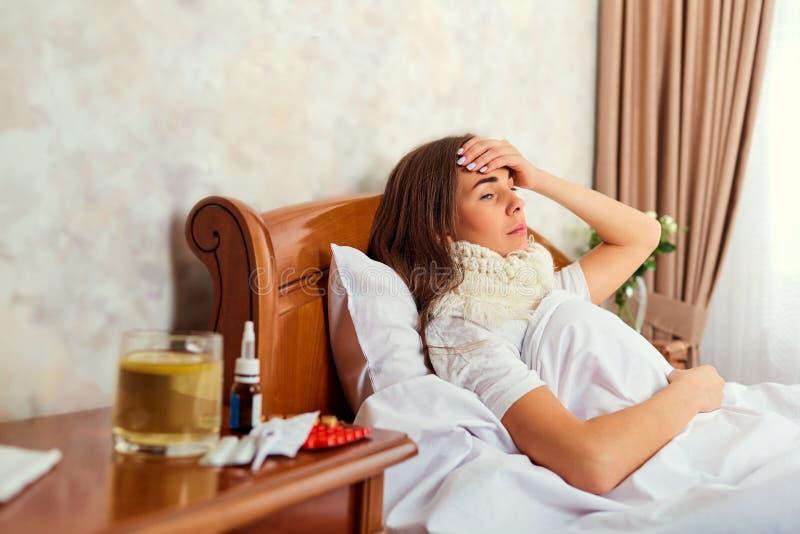 Een zieke vrouw met temperatuur ligt in bed stock foto's