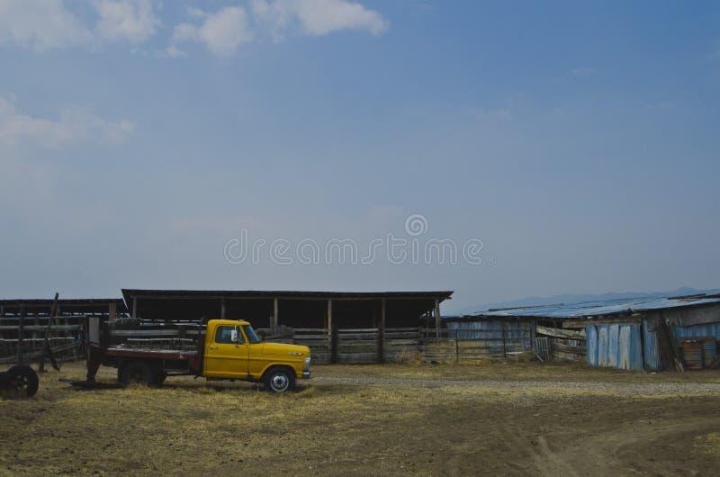 Een zijaanzicht van de loods en de vrachtwagen op het oude landbouwbedrijf stock foto's