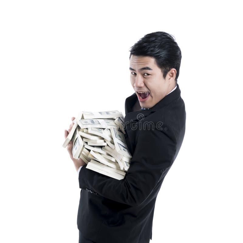 Een zijaanzicht van een jonge zakenman die een grote stapel van bank dragen stock foto's