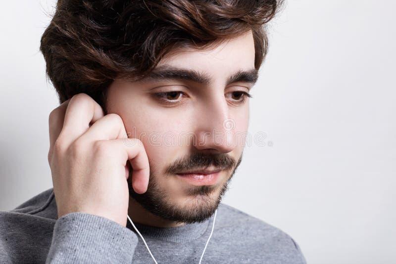 Een zijdelings portret van aantrekkelijke jonge kerel met baard en snor die onderaan het luisteren aan de muziek met oortelefoons stock afbeeldingen