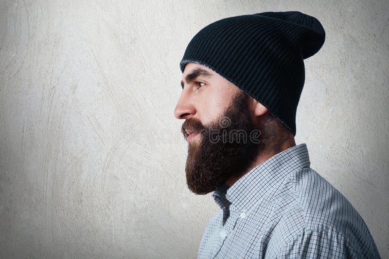 Een zijdelings portret van de modieuze gebaarde mens die gecontroleerd overhemd en zwart GLB dragen die tatoo op zijn hals hebben stock afbeelding