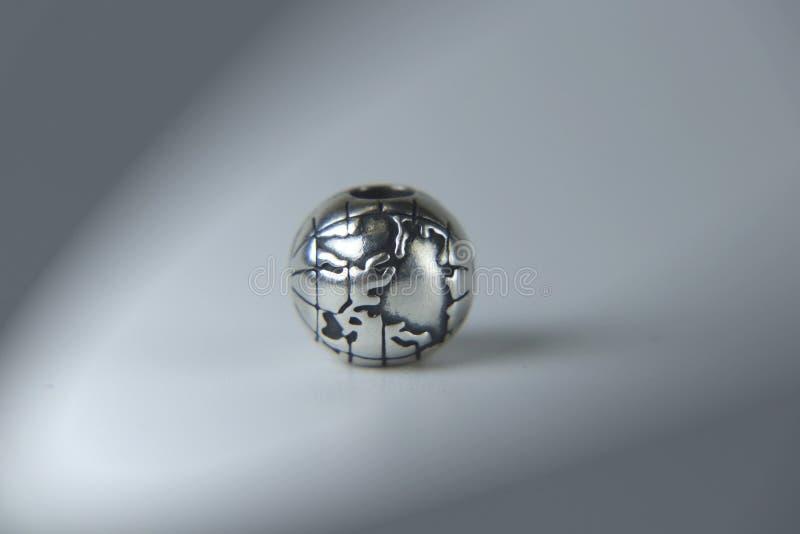 Een zilveren juweel op grijze achtergrond Een aarde als verbazende kettingstoebehoren stock foto