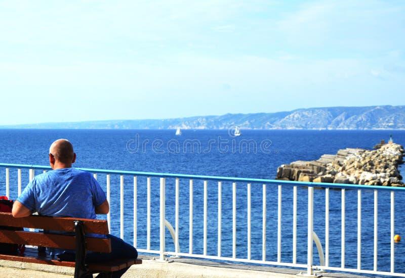 Een zitting van de jonge mensenreiziger op een bank op Mediterrane kust op promenade van Marseille Achtermening van mooi overzees royalty-vrije stock fotografie
