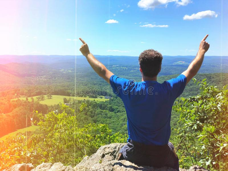 Een zitting van de mensenwandelaar op de de wandelaarzitting van de berga mens op de berg stock afbeelding