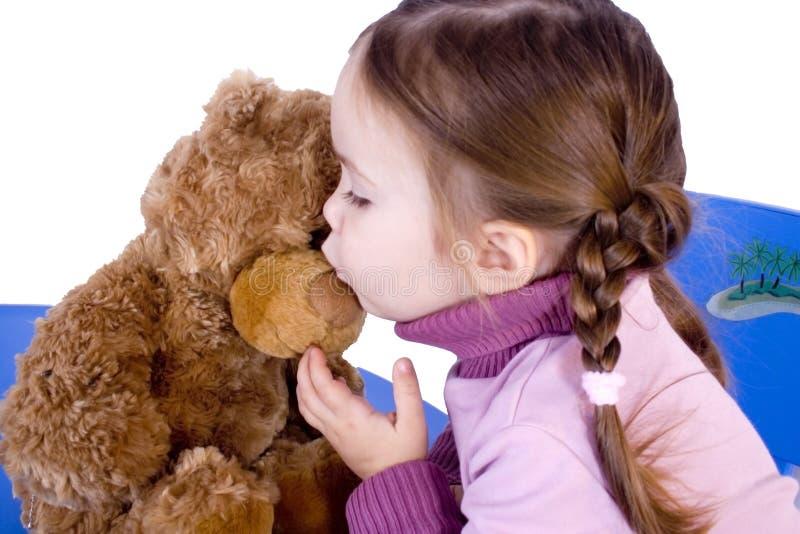 Een zoet babymeisje kust teddy haar royalty-vrije stock foto's