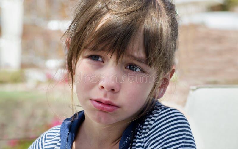 Een zoet meisje pruilde en schreeuwde, beledigd, een kinderachtige gril stock afbeeldingen