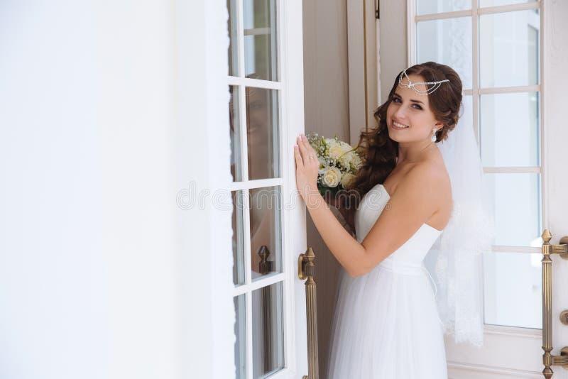 Een zoete bruid in het beeld van een Griekse godin verfraaide haar haar met een revers, nam een kantsluier en een licht huwelijk  stock foto