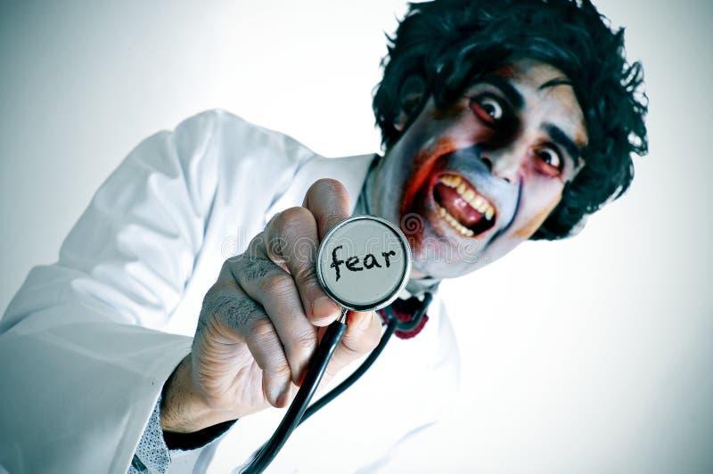 Een zombie arts met de woordvrees in zijn stethoscoop wordt geschreven die royalty-vrije stock afbeeldingen