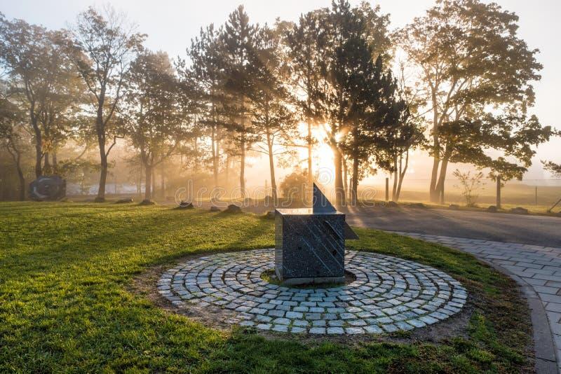 Een zonnewijzer met zonsopgang en silhouetten van bomen royalty-vrije stock afbeelding