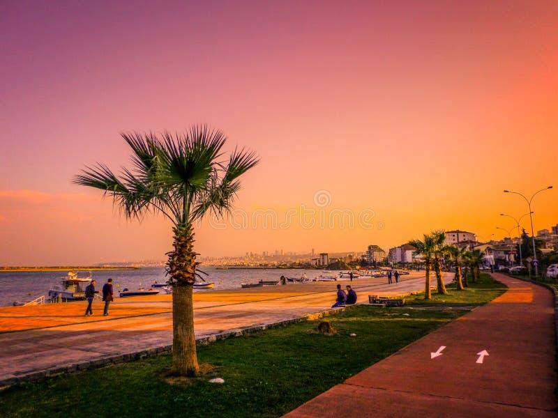 Een zonnige dag bij Atakum-Strand, boten door het overzees en de mensen die op het strand lopen en de fietsweg naast de palmen stock foto