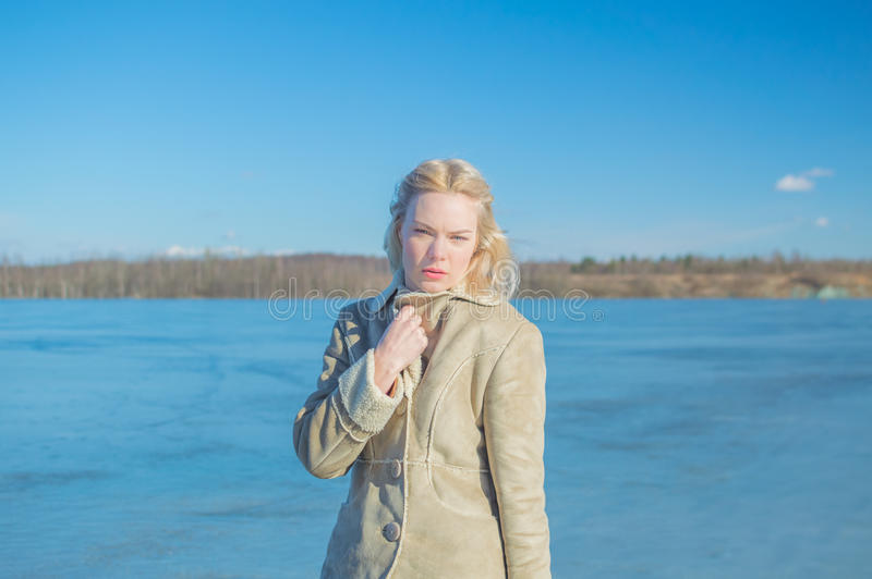 Een Zonnige dag dichtbij het meer, en een mooi die meisje in w wordt verpakt royalty-vrije stock foto