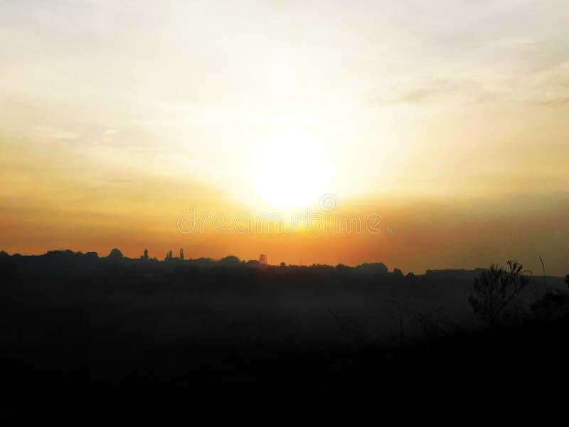 Een zonsondergang in de hemel wordt gefotografeerd aangezien het een gouden gloed aan de hemel die geeft stock afbeelding