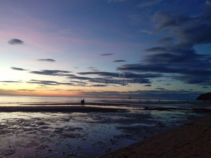 Een zonsondergang op strandmensen het lopen stock foto