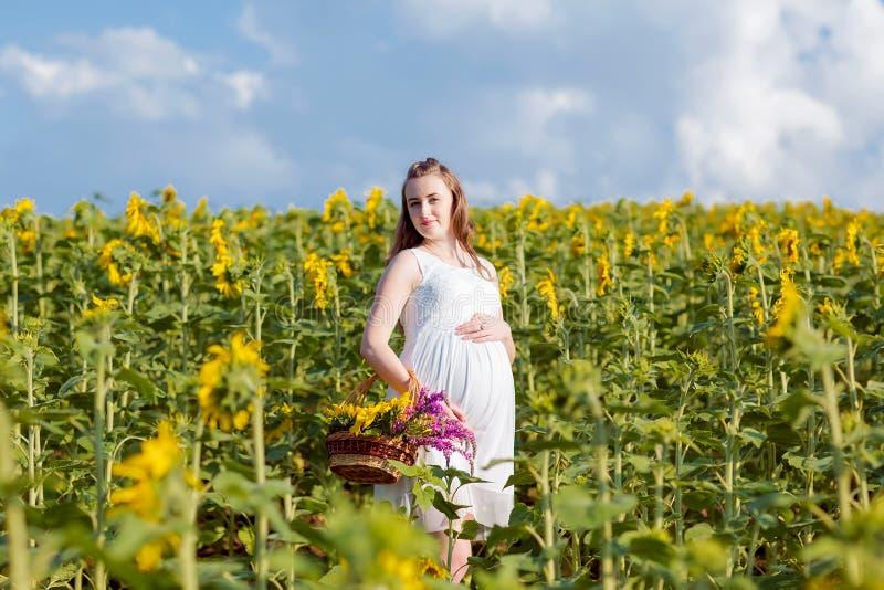Een zwanger meisje in kleding bevindt zich met een mand van bloemen Een meisje bevindt zich met een gele zonnebloem op het gebied stock foto's