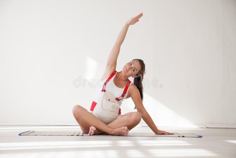 Een zwangere vrouw is bezig geweest met gymnastiek en yoga stock fotografie