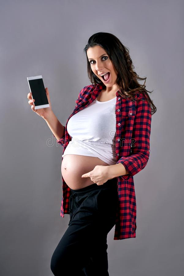 Een zwangere vrouw die haar buik en en een telefoon tonen stock foto's