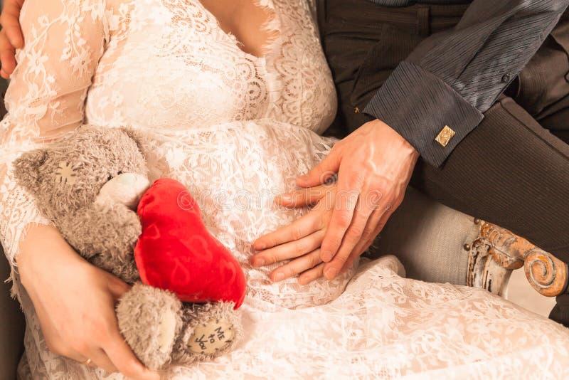 Een zwangere vrouw houdt buiten in haar handen Close-up stock afbeeldingen