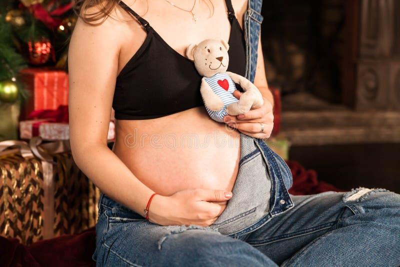 Een zwangere vrouw houdt buiten in haar handen Close-up stock fotografie