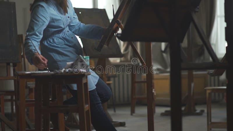 Een zwangere vrouw wordt geïnspireerd om een beeld te schilderen Een vrouwenschilder stock afbeelding