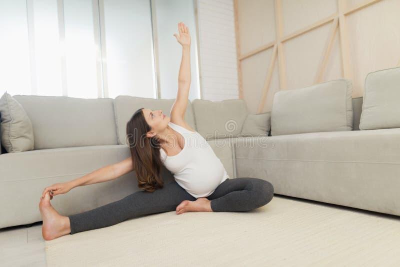Een zwangere vrouw zit thuis op een lichte vloer Zij doet yogaoefeningen stock foto's