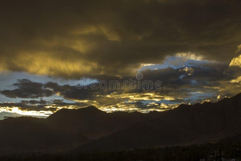 Een zware multicolored zonsonderganghemel over de silhouetten van de bergen royalty-vrije stock afbeelding