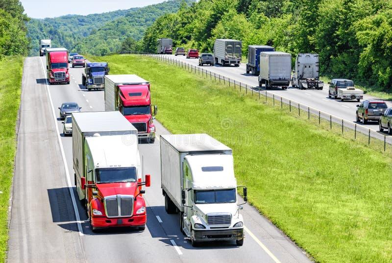 Een zware stroom van 18 speculanten peppered met auto's en SUVs-broodje onderaan een weg tusen staten van Tennessee stock foto's