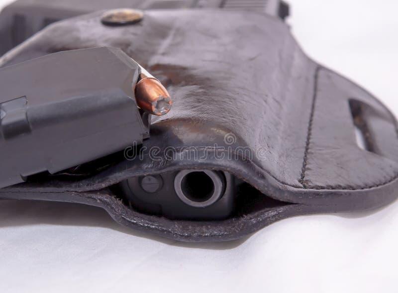 Een zwart die 9mm pistool in een leerholster met een tijdschrift met hol punt wordt geladen bullets bovenop het royalty-vrije stock afbeeldingen