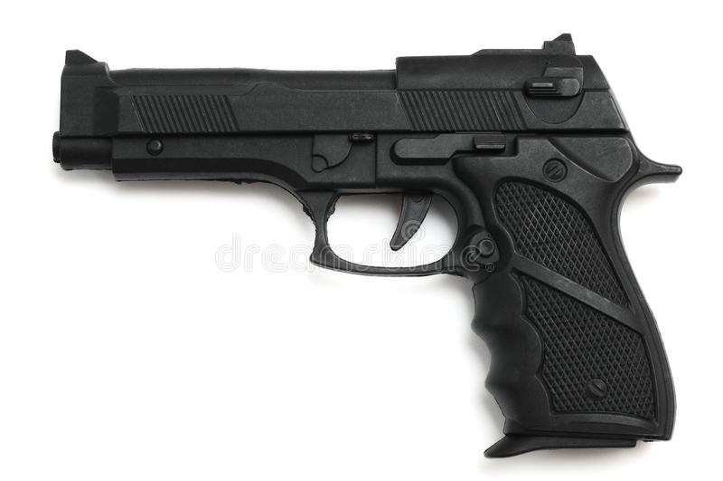 Een zwart hammerless stuk speelgoed pistool tegen een witte achtergrond stock foto